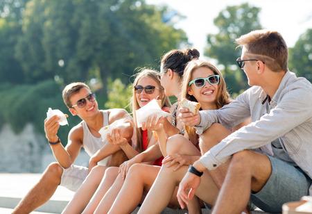 nice food: дружба, отдых, лето и люди концепции - группа улыбающихся друзей в темных очках, сидя с едой на городской площади