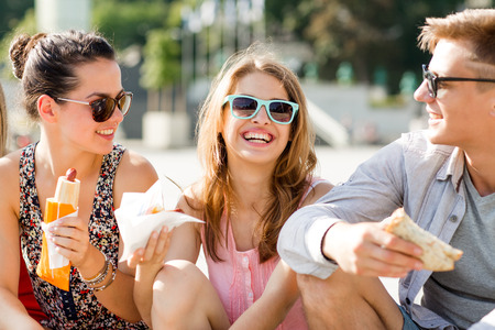 hot guy: friendship, leisure, summer and people concept - group of smiling friends in sunglasses sitting with food on city square