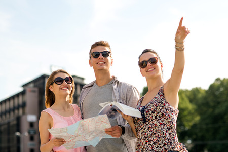 tourist guide: friendship, travel, tourism, vacation and people concept - smiling friends with map and city guide pointing finger outdoors