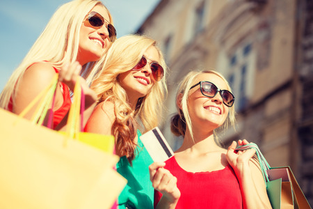 holiday spending: sale and tourism, happy people concept - beautiful blonde women with shopping bags in the ctiy