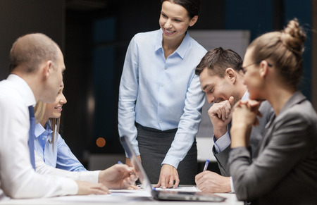 business, technology and office concept - smiling female boss talking to business team photo