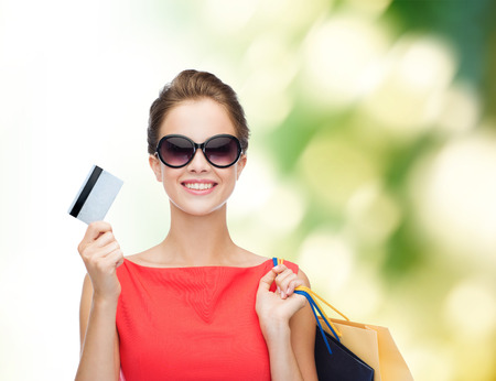 woman holding card: shopping, sale, christmas and holiday concept - smiling elegant woman in red dress with shopping bags and plastic card