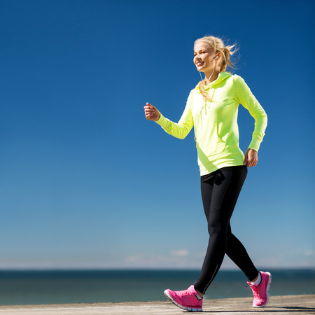 fitness and lifestyle concept - woman walking outdoors photo