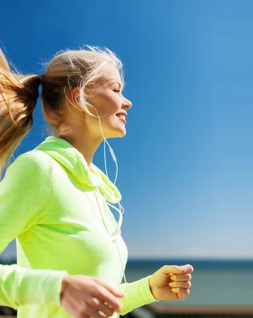 la escucha activa: deporte y estilo de vida concepto - Mujer que hace correr con los auriculares al aire libre Foto de archivo