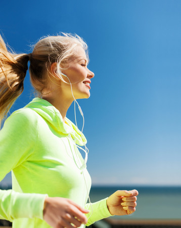 runner girl: sport and lifestyle concept - woman doing running with earphones outdoors