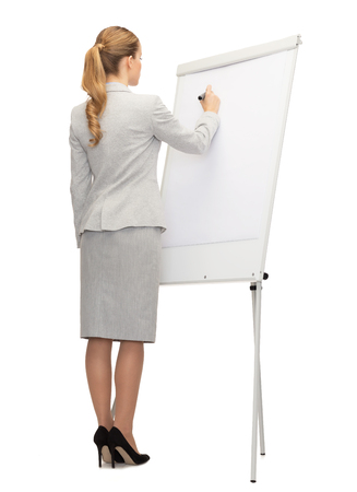 business, education and office concept - businesswoman or teacher with marker writing or drawing something imaginary on whiteboard from back photo