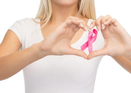 cancer de mama: cuidado de la salud y la medicina concepto - mujer joven en blanco camiseta blanca con la cinta de la conciencia del cáncer de pecho que muestra la forma del corazón Foto de archivo