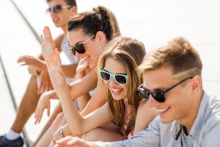 riendo: amistad, ocio, verano, el gesto y el concepto de la gente - grupo de amigos riendo sentada en plaza de la ciudad