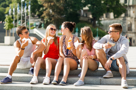 discussing: friendship, leisure, summer and people concept - group of smiling friends in sunglasses sitting with food on city square