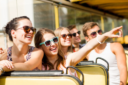 travelers: friendship, travel, vacation, summer and people concept - group of smiling friends traveling by tour bus