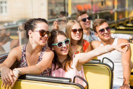out in town: friendship, travel, vacation, summer and people concept - group of smiling friends traveling by tour bus