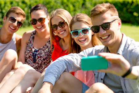 taking: friendship, leisure, summer, technology and people concept - group of laughing friends with smartphone making selfie in park