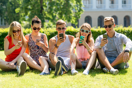 cell phones: friendship, leisure, summer, technology and people concept - group of smiling friends with smartphones sitting on grass in park