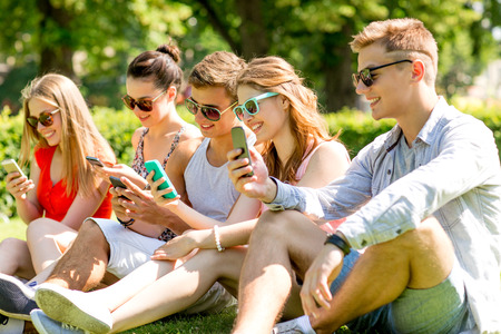 out in town: friendship, leisure, summer, technology and people concept - group of smiling friends with smartphones sitting on grass in park