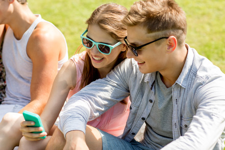 friendship, leisure, summer, technology and people concept - group of smiling friends with smartphone sitting on grass in park photo
