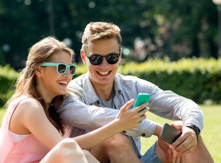 making fun: friendship, leisure, summer, technology and people concept - group of smiling friends with smartphone sitting on grass in park Stock Photo