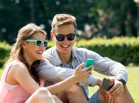 amie: l'amitié, les loisirs, l'été, la technologie et les gens notion - groupe d'amis en souriant smartphone assis sur l'herbe dans le parc Banque d'images