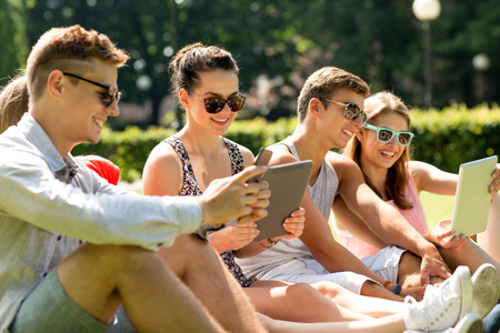 friendship, leisure, summer, technology and people concept - group of smiling friends with tablet pc computers and smartphone sitting on grass in park photo