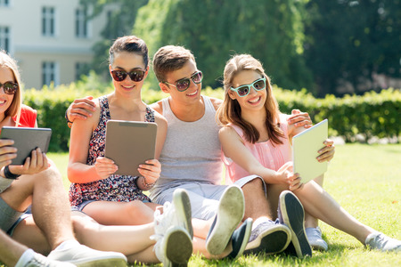 friendship, leisure, summer, technology and people concept - group of smiling friends with tablet pc computers sitting on grass in park photo