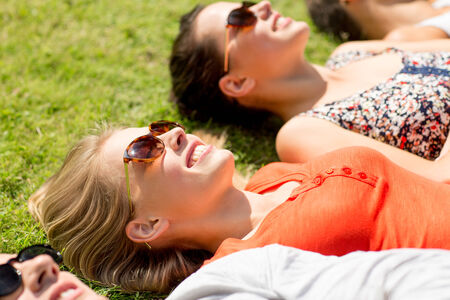 teen couple: friendship, leisure, summer and people concept - group of smiling friends lying on grass outdoors