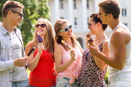 friendship, leisure, sweets, summer and people concept - group of smiling friends with ice cream outdoors