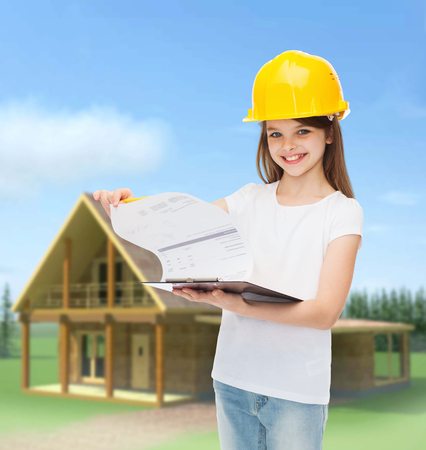 childhood, construction, architecture, building and people concept - smiling little girl in protective helmet with clipboard turning page photo