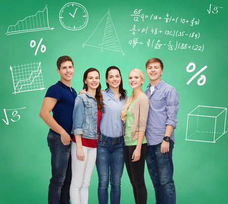 High school student: education, friendship and people concept - group of smiling students standing over green board Stock Photo