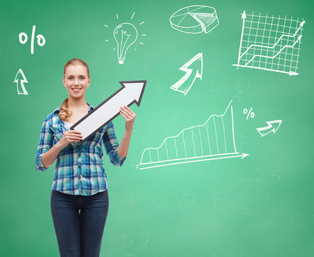 education, direction and people concept - smiling student girl with white arrow pointing up over green board background photo