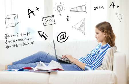 distant: home, education, technology and internet concept - busy teenage girl lying on the couch with laptop computer, book and notebooks at home Stock Photo