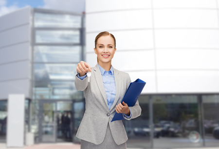 business, real estate, property and office concept - smiling businesswoman with folder and keys photo