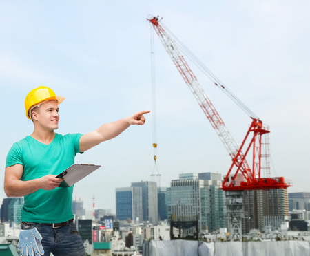 repair, building, construction and maintenance concept - smiling man in helmet with clipboard pointing finger photo
