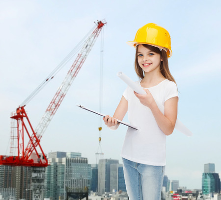 childhood, construction, architecture, building and people concept - smiling little girl in protective helmet with clipboard and blueprint photo