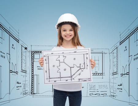 building, childhood, developing, construction and architecture concept - smiling little girl in white helmet showing blueprint photo