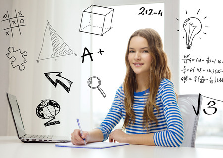 homework student: education, technology and home concept - smiling teenage girl with laptop computer, notebook and pen at home