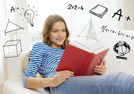 leisure, education and home concept - smiling teenage girl in glasses reading book and sitting on couch at home photo