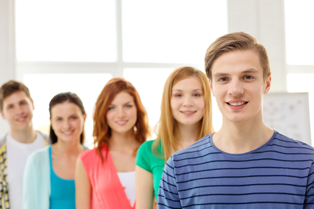 passed test: education and school concept - group of smiling students with teenage boy in front