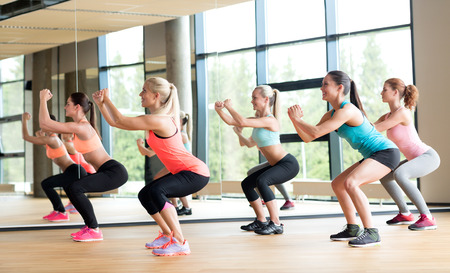 aerobics: fitness, sport, training, gym and lifestyle concept - group of women working out in gym