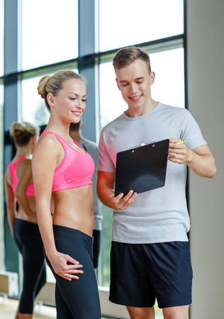 diet plan: fitness, sport, exercising and diet concept - smiling young woman with personal trainer in gym