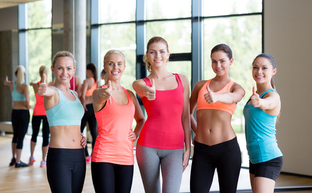 fitness, sport, friendship and lifestyle concept - group of women showing thumbs up gesture in gym photo
