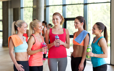 fitness, sport, training, gym and lifestyle concept - group of women with bottles of water in gym photo