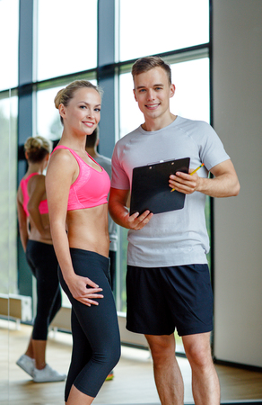 weight loss plan: fitness, sport, exercising and diet concept - smiling young woman with personal trainer in gym