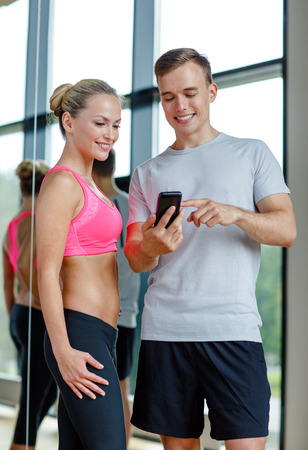 fitness, sport, exercising, technology and diet concept - smiling young woman and personal trainer with smartphone in gym photo