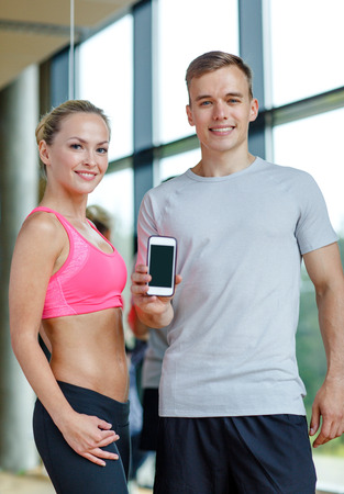 fitness, sport, advertising, technology and diet concept - smiling young woman and personal trainer with smartphone blank screen in gym photo