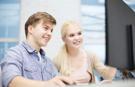 teenage guy: technology, school and education concept - smiling teenage boy and girl in computer class at school