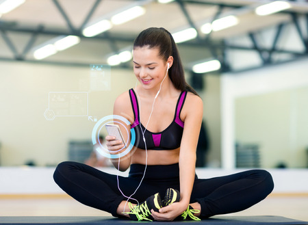 fitness, sport, training, technology and lifestyle concept - smiling young woman with smartphone and earphones in gym photo