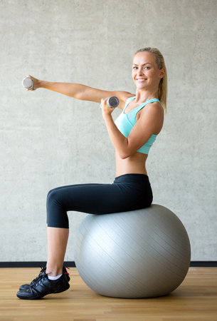 fit ball: fitness, sport, training and lifestyle concept - smiling woman with dumbbells and exercise ball in gym Stock Photo