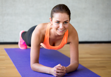 woman buttocks: fitness, sport, training and lifestyle concept - smiling woman doing exercises on mat in gym