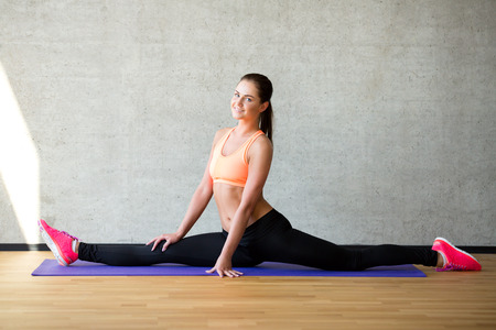 gym class: fitness, sport, training and lifestyle concept - smiling woman stretching leg on mat in gym Stock Photo