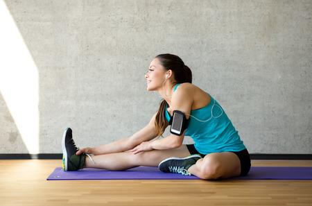 trabjando en casa: fitness, deporte, entrenamiento y estilo de vida concepto - mujer sonriente que se extiende la pierna sobre la colchoneta en el gimnasio