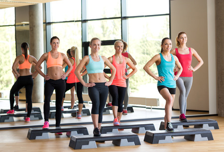 fitness, sport, training, gym and lifestyle concept - group of women working out with steppers in gym Banco de Imagens